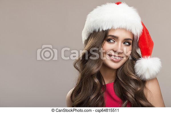 Retrato de atractiva mujer sonriente con sombrero de Santa. Antecedentes grises. - csp64815511