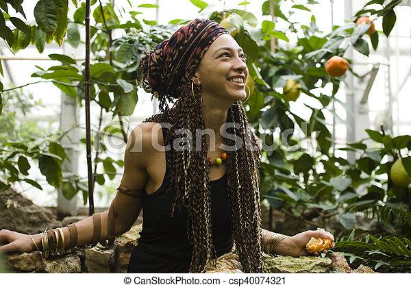Una joven mujer sonriente en el parque con naranjas - csp40074321