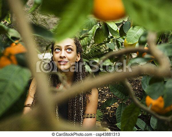 Una joven mujer sonriente en el parque con naranjas - csp43881313