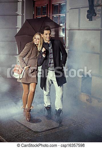 Bonita pareja con un paraguas enorme - csp16357598