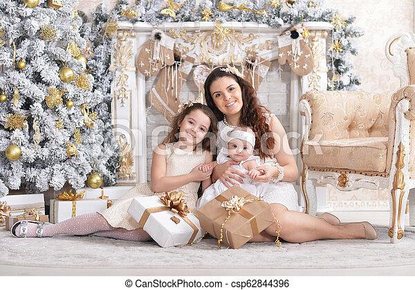 Retrato de madre feliz con hijas bonitas posando - csp62844396