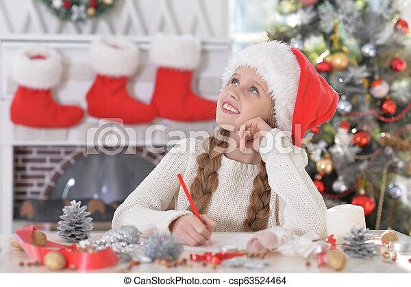 Linda niña con sombrero de Santa preparándose para Navidad en casa - csp63524464