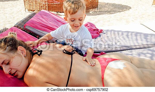 Foto de niño lindo de 3 años haciendo masajes a madre joven relajándose en el lecho solar de la playa - csp69757902