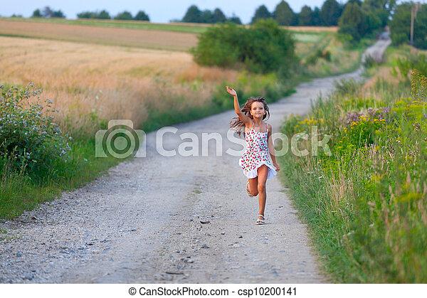 Una linda chica de siete años corriendo por el camino de los bosques el día del verano - csp10200141