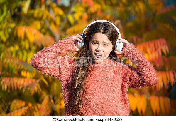 Listening audio best way help child improve vocabulary. Kid girl relaxing near autumn tree with headphones. Autumn walks with nice songs. Music for autumn mood. Listening song. Enjoy music fall day - csp74470527
