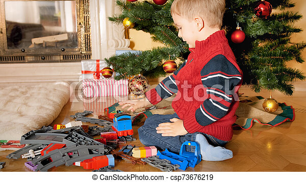 Little 4 years old boy sitting on floor under Christmas tree and building toy railroad - csp73676219