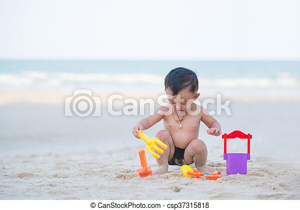 Little Asian boy 1 year old playing sand on the beach - csp37315818
