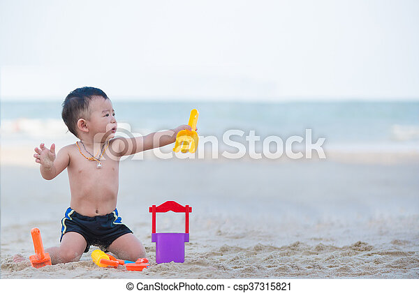 Little Asian boy 1 year old playing sand on the beach - csp37315821