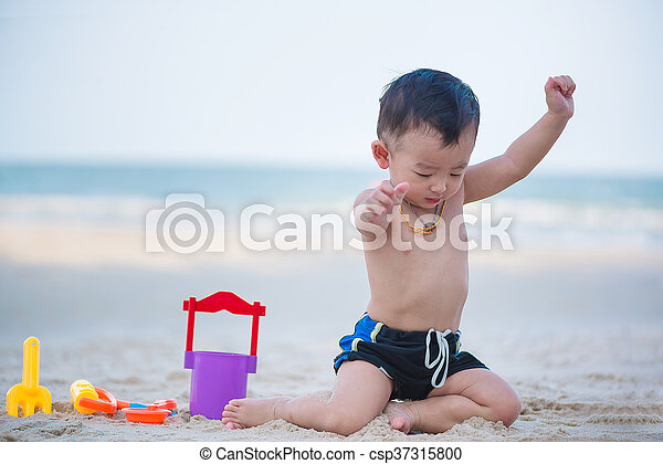 Little Asian boy 1 year old playing sand on the beach - csp37315800