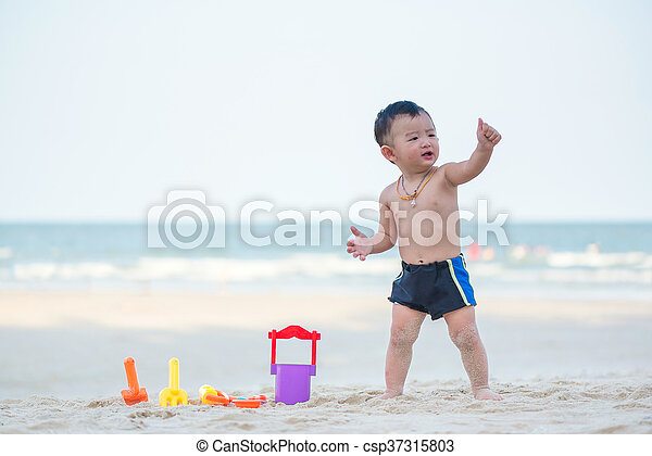 Little Asian boy 1 year old playing sand on the beach - csp37315803