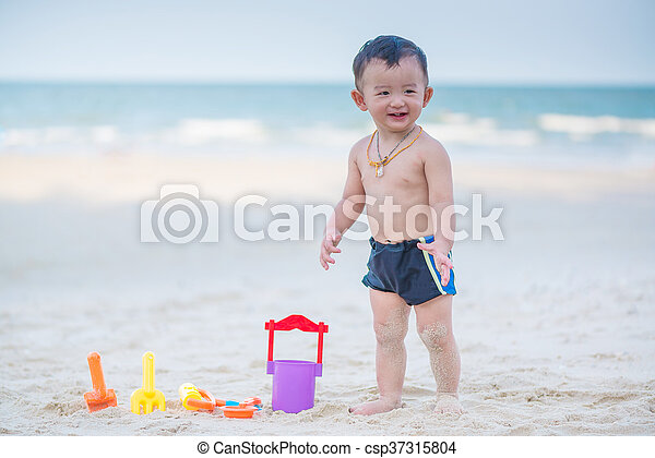 Little Asian boy 1 year old playing sand on the beach - csp37315804