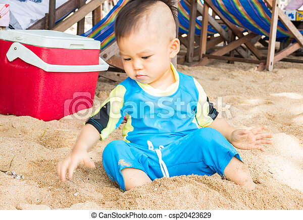 Little asian boy playing sand on the beach - csp20423629
