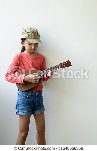 Little Asian girl playing ukulele - csp48656356