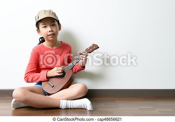 Little Asian girl playing ukulele - csp48656621