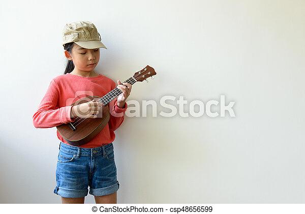 Little Asian girl playing ukulele - csp48656599