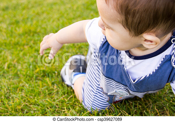 little baby learning to crawl on the grass a Sunny summer day. the concept of children's development by months. happy child playing in the Playground - csp39627089