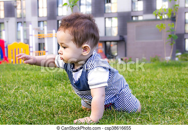 little baby learning to crawl on the grass on a Sunny summer day. the concept of children's development by months. happy child playing in the Playground - csp38616655