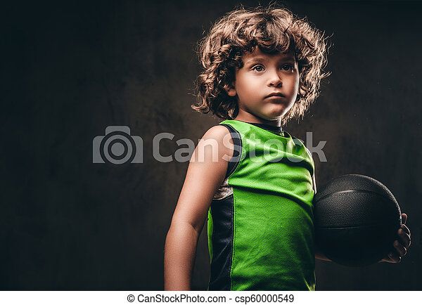 Little basketball player in sportswear holding ball in a studio. Isolated on the dark textured background. - csp60000549