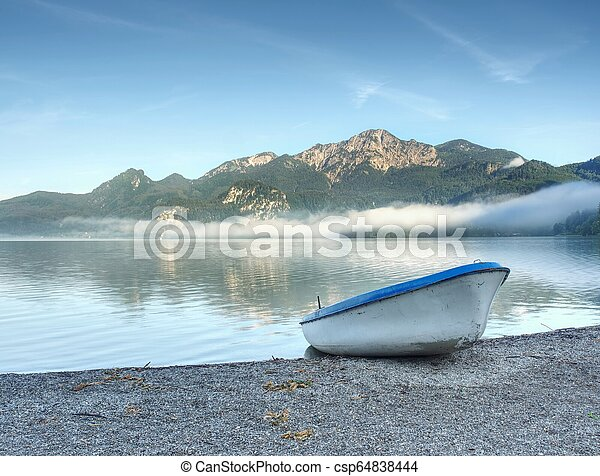 Little boat on lake shore, beautiful summer nature. - csp64838444