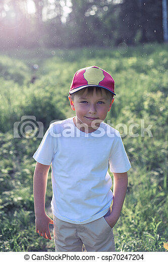 Little boy 7 years walking in the woods at sunset - csp70247204