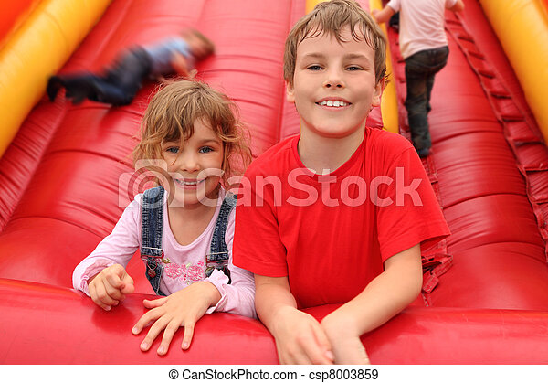 little boy and girl lying on red inflatable slide, smiling and looking at camera - csp8003859
