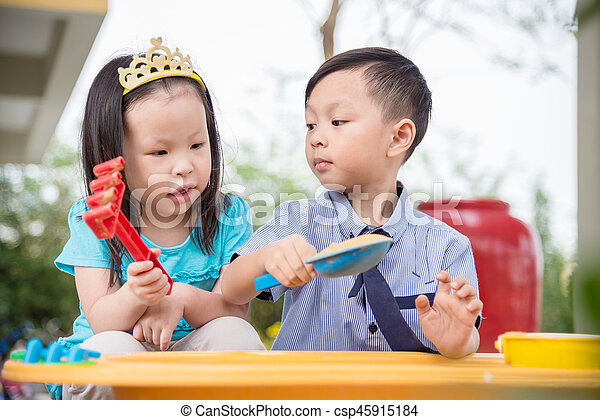 Little boy and girl playing sand in sandbox together - csp45915184