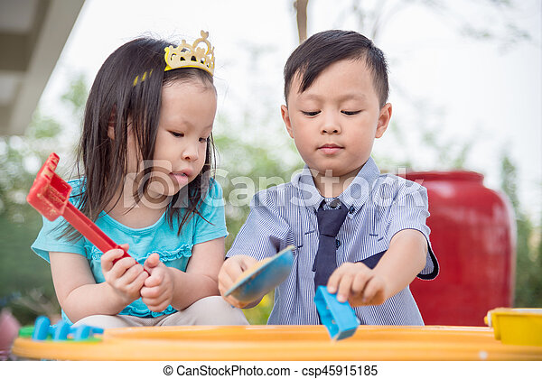 Little boy and girl playing sand in sandbox together - csp45915185