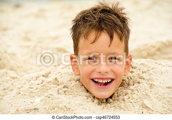 little boy buried in the sand on beach - csp46724553