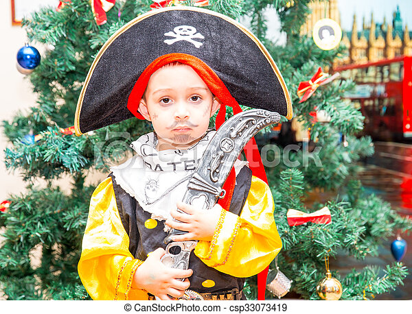 Little boy child dressed as pirate for Halloween  on background of Christmas tree  - csp33073419