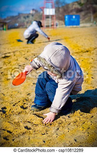 little boy digs in sand - csp10812289