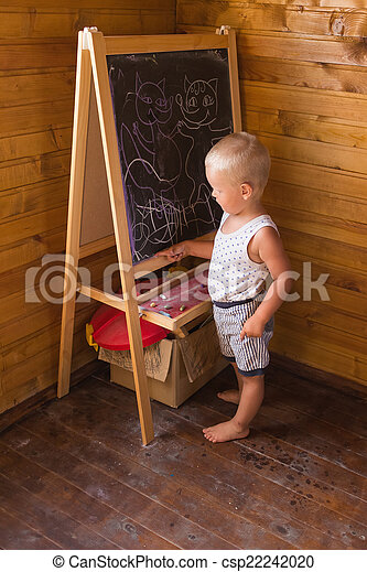 Little boy drawing with chalk on a blackboard - csp22242020