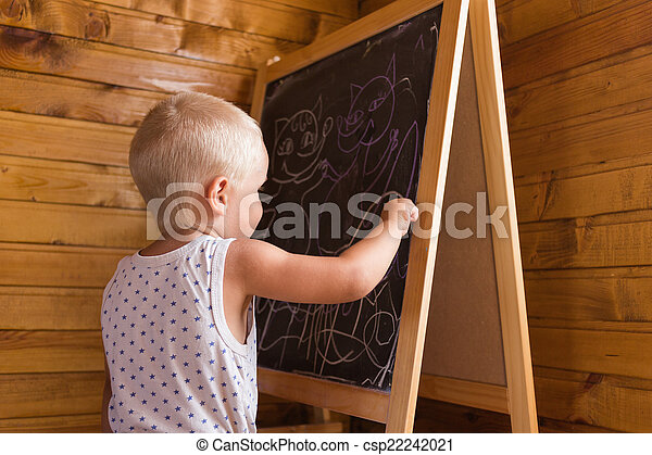Little boy drawing with chalk on a blackboard - csp22242021