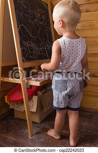 Little boy drawing with chalk on a blackboard - csp22242023