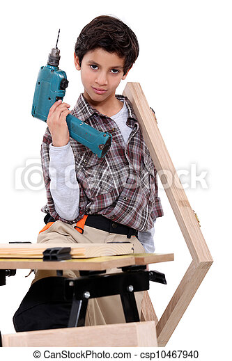 little boy dressed like a craftsman holding a drill - csp10467940