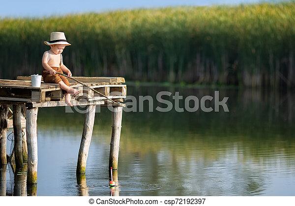 little boy fishing on the lake - csp72192397