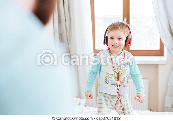 Little boy in headphones listening to music standing on bed - csp37031812