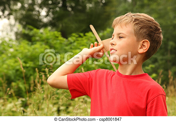 little boy in red T-shirt plays with wooden airplane on nature - csp8001847