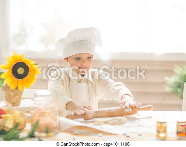 little boy in the form of a cook rolls out the dough in the kitchen - csp41011106