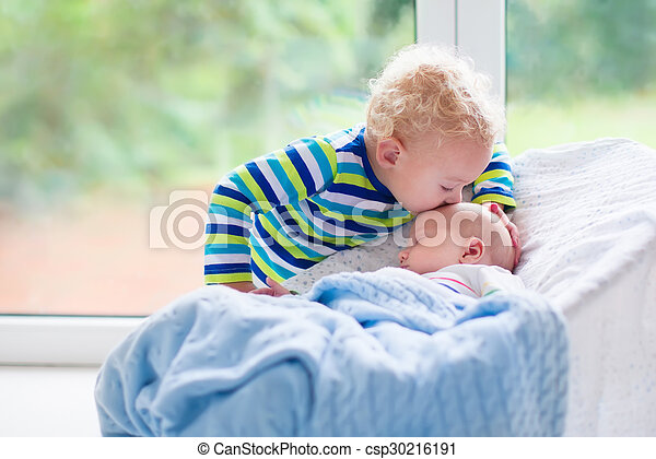 Little boy kissing newborn baby brother - csp30216191