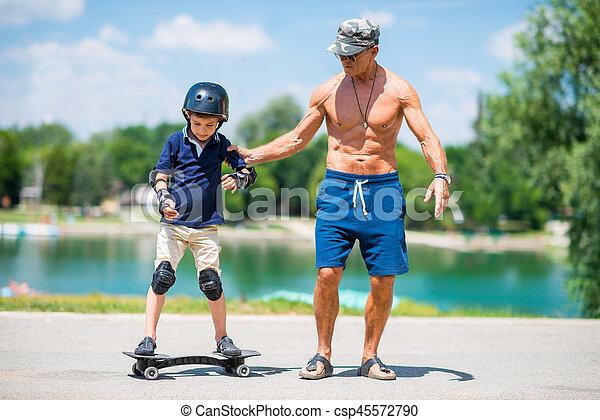 Little boy learning snakeboard, grandpa helping - csp45572790