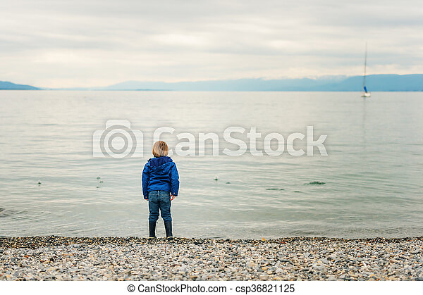 Little boy playing by the lake on a cloudy day - csp36821125
