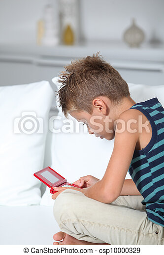 Little boy playing video games on sofa - csp10000329