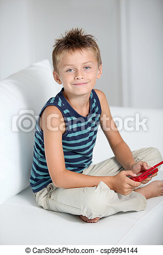 Little boy playing video games on sofa - csp9994144