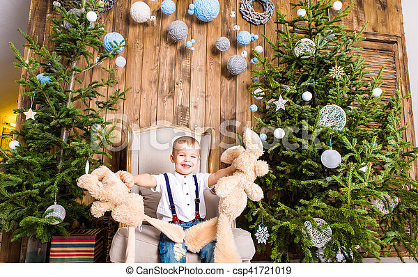 Little boy playing with toy at home near the Christmas tree. - csp41721019