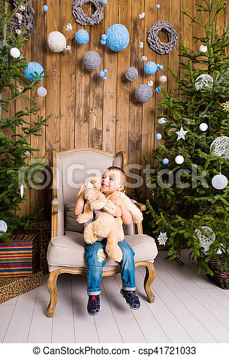 Little boy playing with toy at home near the Christmas tree. - csp41721033