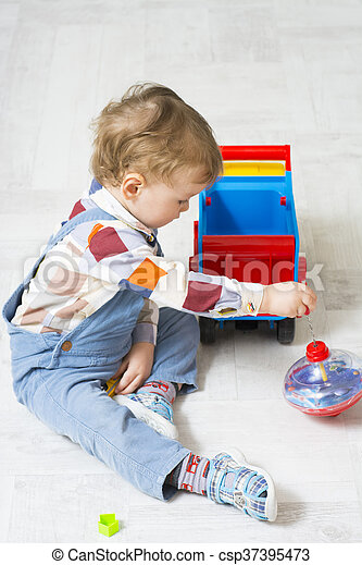 Little boy plays with a car and spinning top toy - csp37395473