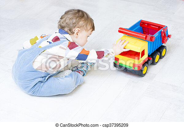 Little boy plays with a car and spinning top toy - csp37395209