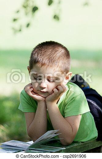 Little boy reading book in park - csp2691906