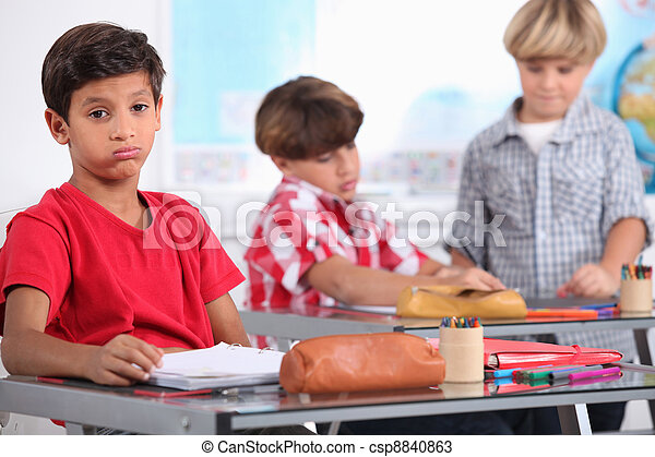 little boy sighing in a classroom - csp8840863