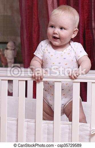 Little boy sitting in a crib - csp35729589